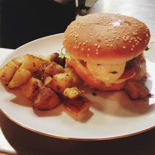 Plat de Hamburger au boeuf fromages italiens, petits légumes marinés et salade de légumes frais et potatos