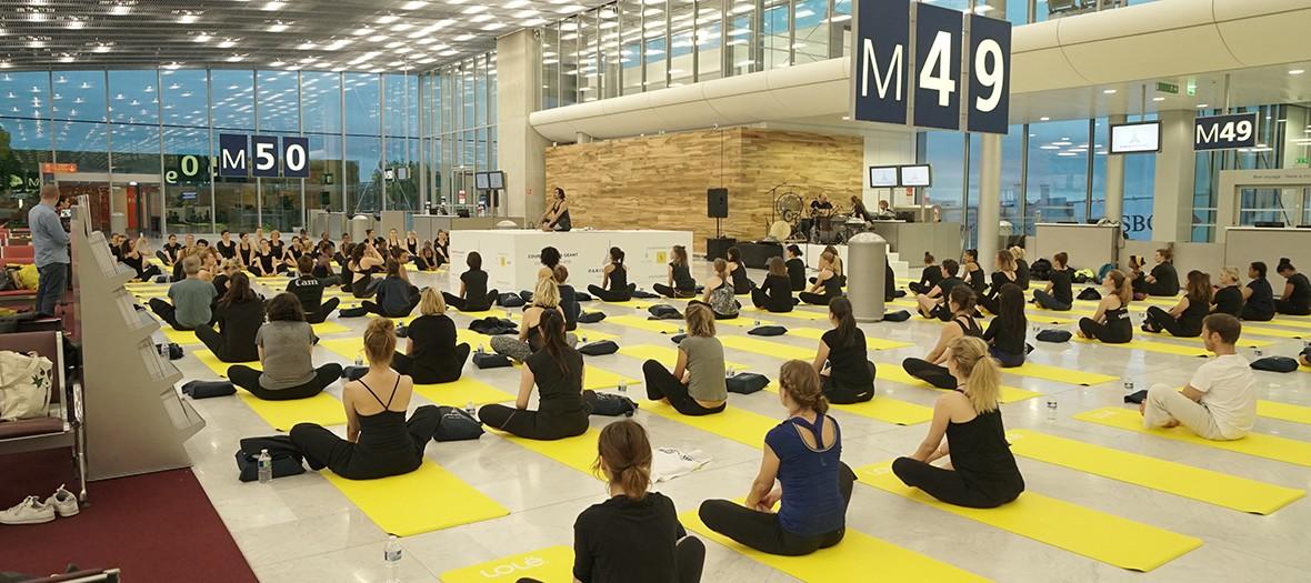 personnes faisant du yoga en salle d'embarquement