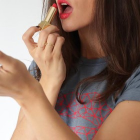 Girl putting on red lipstick