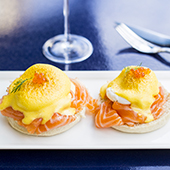 Poed Benedict egg drizzled with hollandaise sauce, served veggie, bacon with salmon