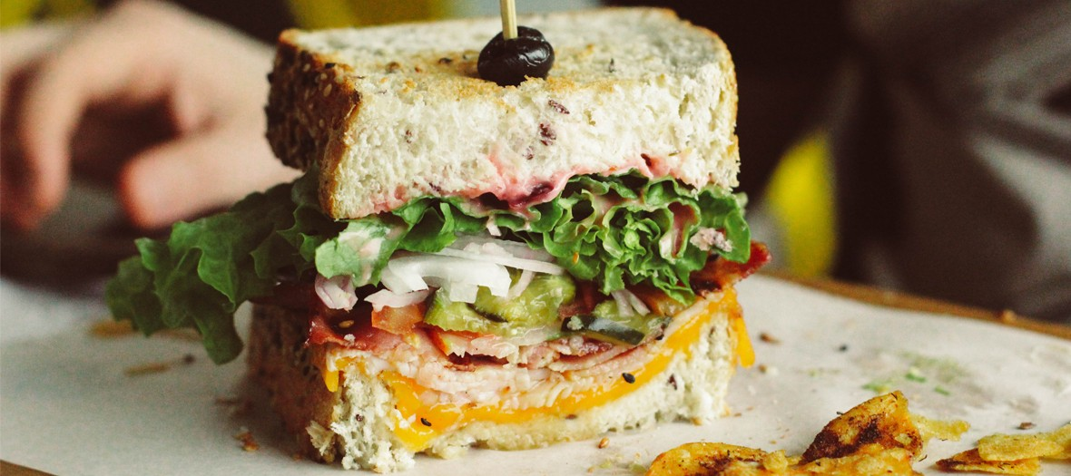 Sandwich with bread, salad, cheddar, tomatoes, onions, pickle, ham from Club Sandwich