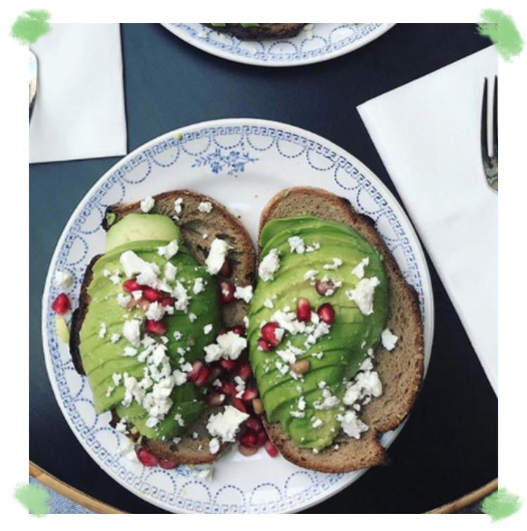 Avocado toast avec fromage frais, grenade et salade de roquette