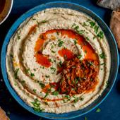Houmous a l'harissa avec de la sauce Tabasco rouge et comme accompagnements des legumes et du pain