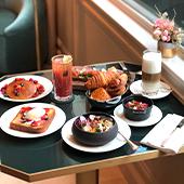 Façade de l'Hôtel Grand Powers et table de petit dejeuner avec croissant, viennoiserie, fruit et jus de fruit