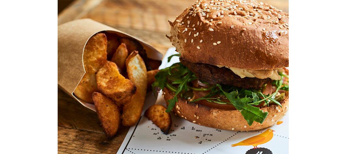 Plat de burger avec oignons, cornichon, pousse de graine germées et feuille de chêne et Frites