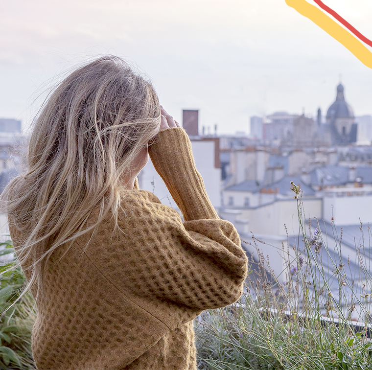 Young girl watching Paris from the au top rooftop in Paris