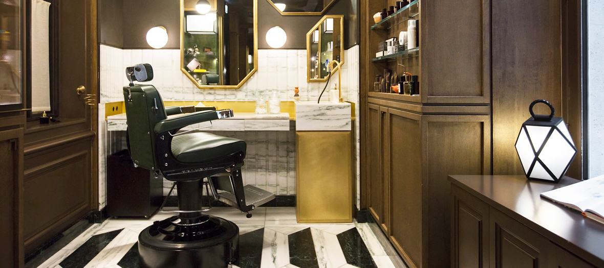 A salon with a unique barber seat all in brass, marble and tobacco-coloured walls where a barber razor pro clips and cuts the style of Parisians