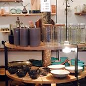 Décoration de L'Atelier Mano avec des vases, des gobelets graphiques en carton, de petites céramiques japonaises, des assiettes et du sel de mer