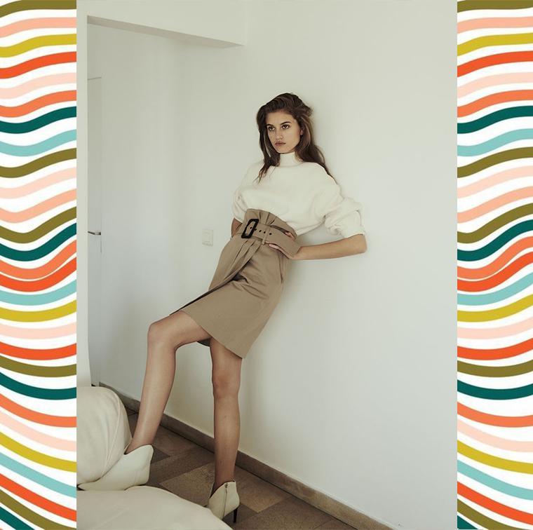 Jupe portefeuille marron avec ceinture, pull en laine et coton blanc col rond, bottines blanches pointues en cuir