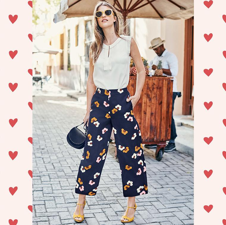 Pantalon jambes larges bleu marine et motif fleurs, chaussures à talons en daim jaune, mini sacoche bleu marine en cuir, lunettes de soleil jaune oversize
