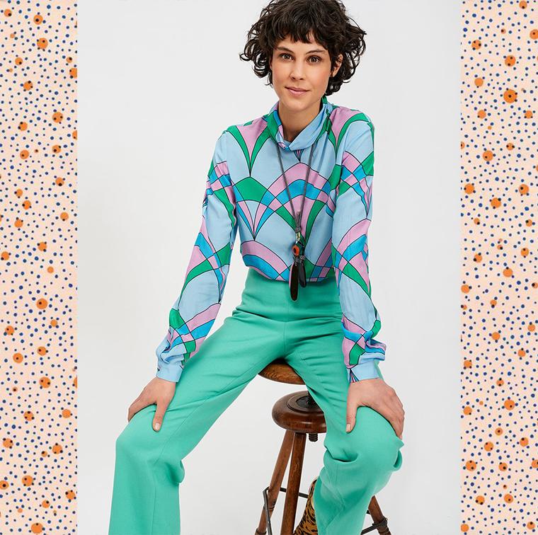 Chemisier avec imprimé graphique bleu, rose et vert, pantalon droit cyan, collier pendentif oeil multicolore