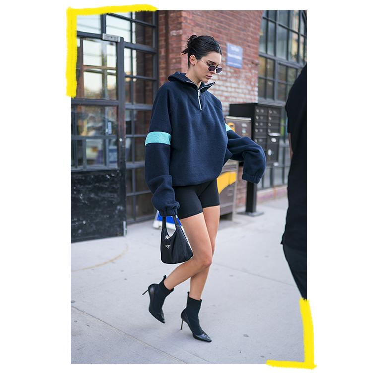 Cycliste, gros pull, sac Prada, boots chaussettes bi-matière talon aiguille