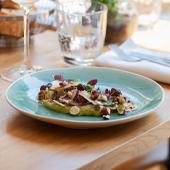 Plat de Carpacio avec du brocoli, sel, poivre, l'huile d'olive, coriandre, noisettes torréfiées