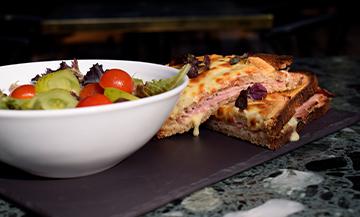 Le Croque Monsieur au jambon à la truffe et gruyère râpé et un bol de salade de la cheffe Juliette de l'Hôtel Parister