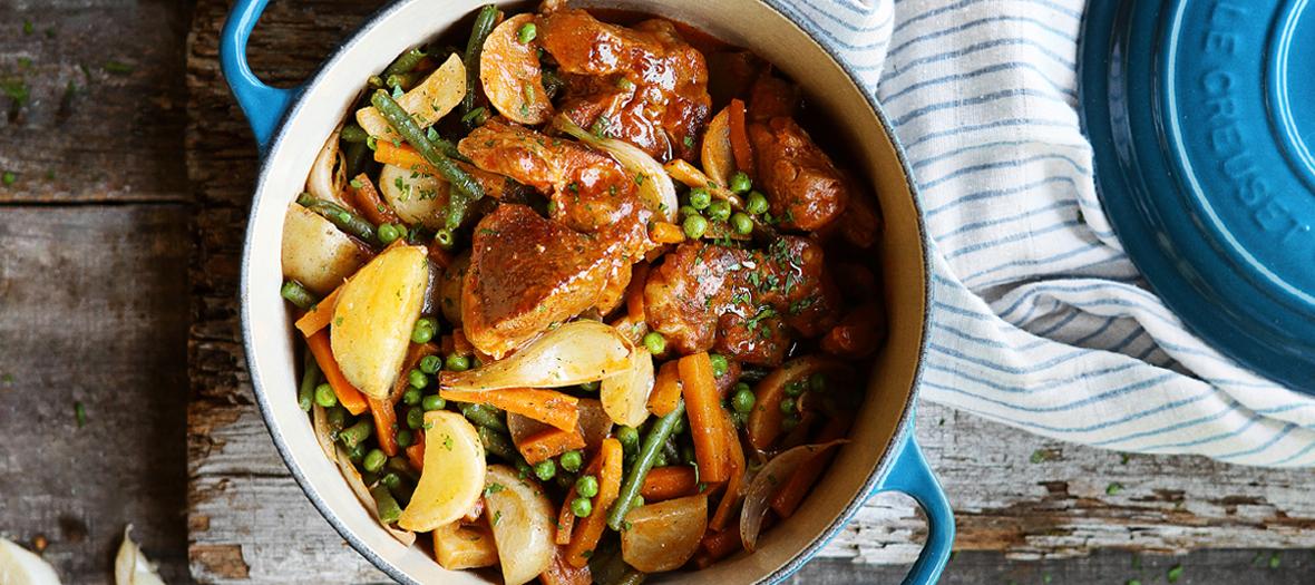 Plat de navarin d'agneau avec navets, carottes, oignons, tomate, haricots verts, pommes de terre, petits pois