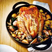 Poulet roti avec de l'oignon, du thym, du laurier, des champignons