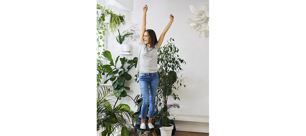 Jeune fille sautant de joie dans son salon