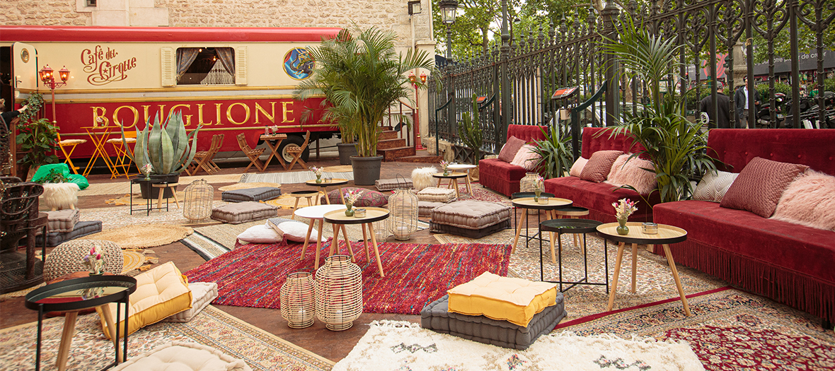Ephemeral terrace of the Gyspy café with Emmanuelle wicker armchair, banquettes, mix and match of burlap carpets, comfy cushions, knit poufs, tropical plants at the Cirque d'Hiver in Paris