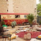 Terrasse éphémère du Gyspy café avec fauteuil Emmanuelle, banquettes crapauds, mix and match de tapis en jute, coussins douillets, poufs en tricot, plantes tropicales dans la cour du Cirque d'Hiver à Paris