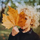Petit garçon avec une feuille d'automne
