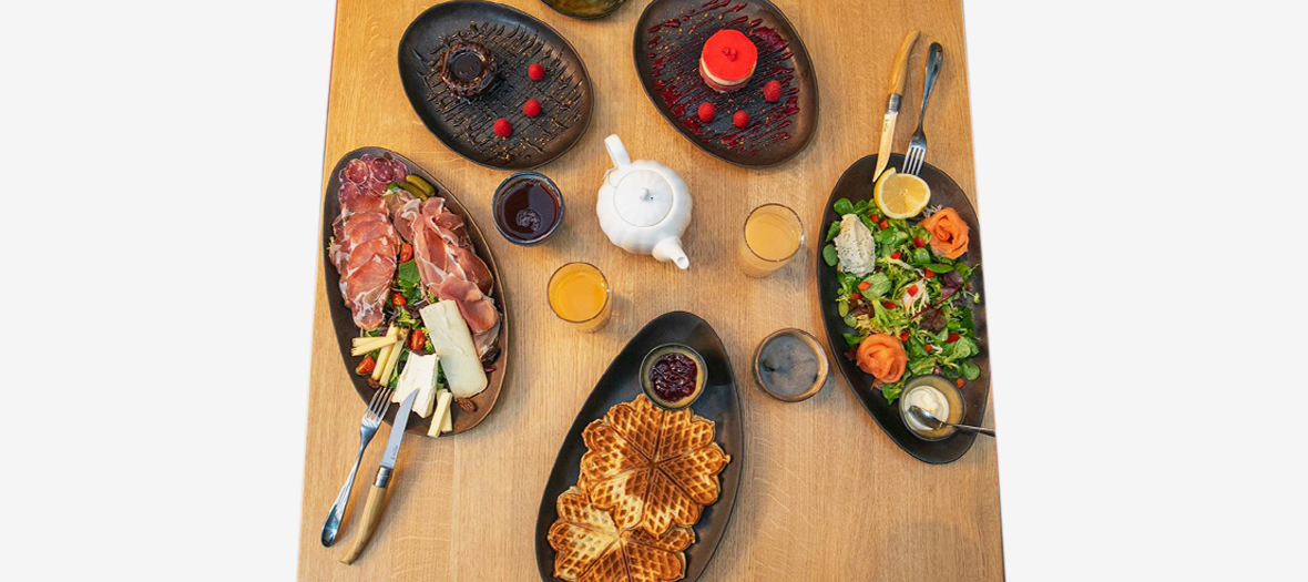Brunch from Assemblages that includes Fresh fruit juices, such as apple-pineapple from the extractor, a Norwegian waffle with cardamom, a fruit salad and a nice charcuterie plate with ham from Auvergne, Corsican coppa, refined A.O.C. cheese or smoked salmon and tarama