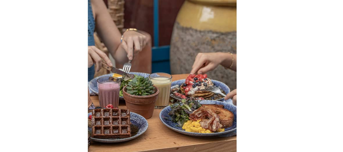 Le brunch de chez Cali Sisters avec des pancakes, un granola, des œufs brouillés, bacon croustillant et le green shakshuka.