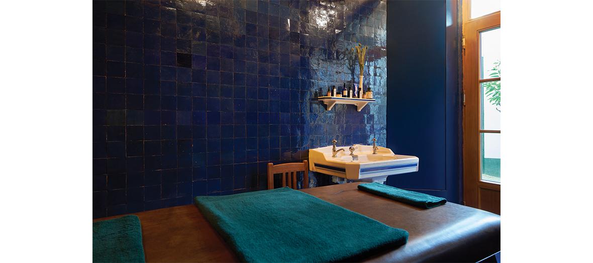 Cabine de massage avec chaise, faïence bleue, table en cuir, savons, huiles et produits de beauté naturels à l'Officine Buly
