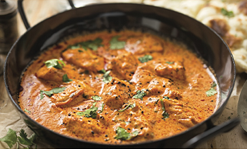 Plat de chicken butter avec poulet, ail, gingembre, oignons, noix de cajou, feuilles de coriandre, tomate, cumin en poudre, poudre de piment