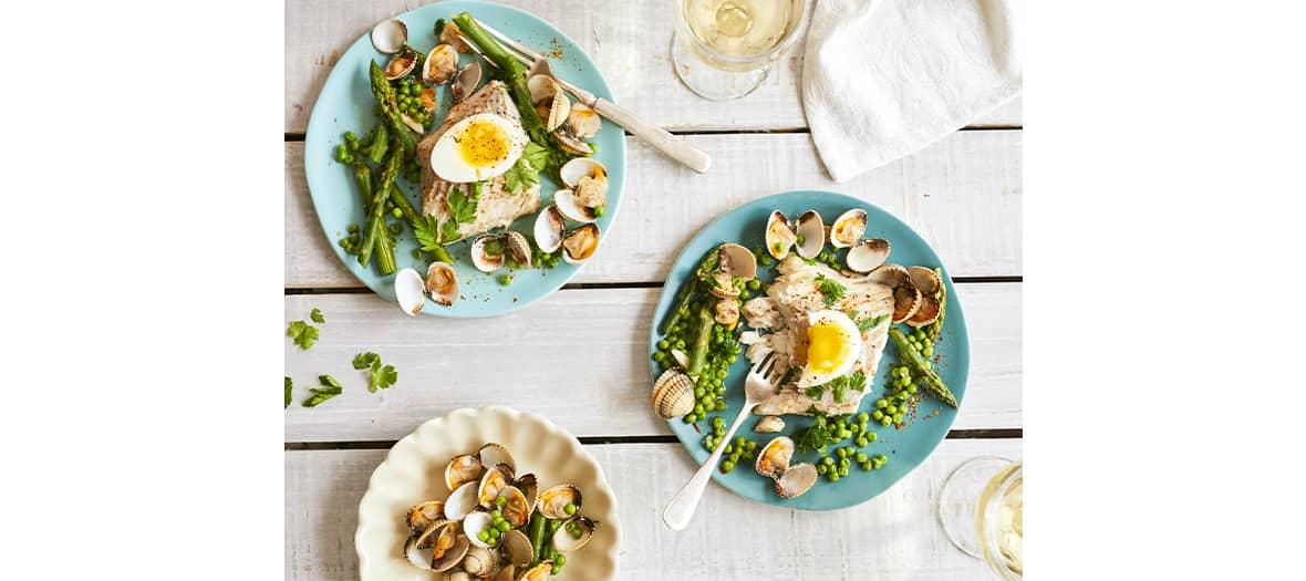 un merlu aux coquillages aux légumes printaniers.